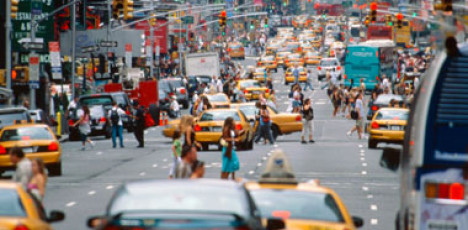 A midtown street busting with cabs and pedestrians.